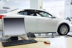计算机在桌和新的白色汽车上站立 库存照片