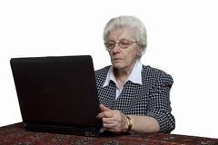 计算机她看起来的老妇人 免版税库存照片