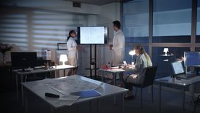 计算机工程师队谈论某事在一个大电视屏幕上在实验室