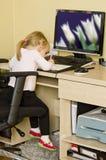 计算机服务台的小女孩 免版税图库摄影