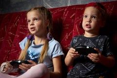 计算机游戏:男孩和女孩在他们的手上播放在黑暗的一个比赛控制台并且拿着gamepads 图库摄影
