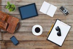 计算机片剂和巧妙的电话有被隔绝的屏幕的在老木书桌上 库存照片