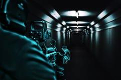 计算机球员在走廊站立和瞄准准直仪范围 免版税库存图片