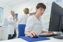 计算机的愉快的女性医生在医房 库存图片