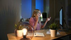 计算机的愉快的女性谈话在智能手机 坐在晚上的方格的衬衣的快乐的惊奇白肤金发的妇女在 股票录像