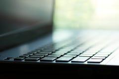 计算机笔记本选择聚焦宏观徒升在键盘的有软的迷离庭院的通过窗口背景 库存图片