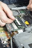 计算机维护` s手从膝上型计算机的里面提取内存 图库摄影