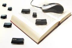 计算机老鼠和钥匙在书传播 免版税库存照片