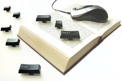 计算机老鼠和钥匙在书传播 免版税库存图片