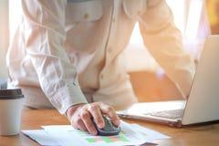 计算机老鼠在手中,人办公室工作人员分析图表 免版税库存图片