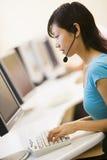 计算机耳机空间坐的佩带的妇女 库存图片