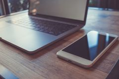 计算机膝上型计算机和流动巧妙的电话有黑屏的在木头 免版税库存图片