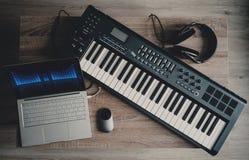 计算机音乐,家庭演播室设备 密地键盘、便携式计算机、耳机和扩音器显示器 库存照片