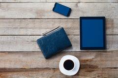 计算机ipad样式和巧妙的电话有被隔绝的屏幕的在老木书桌上 图库摄影