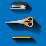 订书机,剪刀,铅笔,在蓝色背景 免版税库存图片