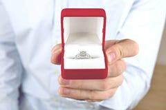 订婚/婚姻/婚礼提案场面 关闭递昂贵的金白金钻戒的人对他的新娘 免版税库存图片