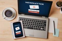 订阅在膝上型计算机和智能手机屏幕上的时事通讯概念 免版税库存照片