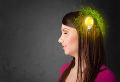 认为与电灯泡的绿色eco能量的年轻头脑 库存照片
