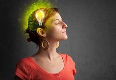认为与电灯泡的绿色eco能量的年轻头脑 免版税图库摄影