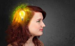 认为与电灯泡的绿色eco能量的年轻头脑 免版税库存图片