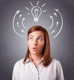 认为与箭头和电灯泡的俏丽的夫人在头顶上 免版税库存照片