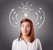 认为与箭头和电灯泡的俏丽的夫人在头顶上 免版税图库摄影