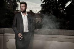 认为与香烟的年轻,英俊的人 免版税库存照片