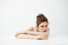 认为乏味疲乏的年轻俏丽的女孩用小圆面包作说谎在白色背景的桌上 图库摄影
