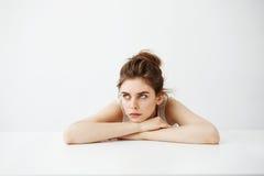 认为乏味疲乏的年轻俏丽的女孩用小圆面包作说谎在白色背景的桌上 库存照片