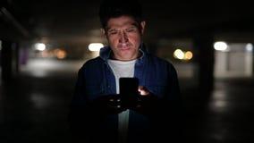 认为可疑的西班牙的人,当使用电话在黑暗的停车场时 股票录像