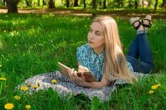 认为和写在她的日志的美丽的女孩在与花的草 正面图 免版税库存图片