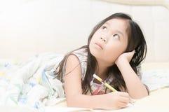 认为和写给日志的逗人喜爱的亚裔女孩在床上 库存照片