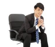 认为和坐在椅子的年轻商人 免版税库存图片