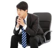 认为和坐在椅子的年轻商人 库存照片