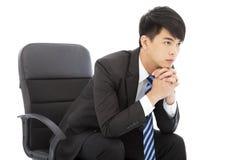 认为和坐在椅子的年轻商人 免版税库存照片