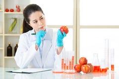 认为和拿着苹果的亚裔女性科学家 库存照片