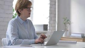 认为和研究膝上型计算机的沉思老妇人 股票录像