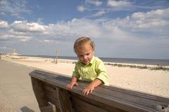 认为在一条靠海滨的长凳的小孩 免版税图库摄影