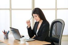 认为在办公室的年轻亚裔女实业家 免版税库存照片