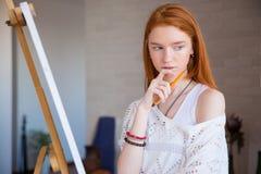 认为在图画班的画架附近的沉思可爱的女性艺术家 免版税图库摄影