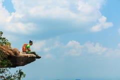 认为在山峰峭壁的妇女远足者 库存照片