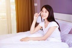 认为在床上的美丽的妇女在卧室 免版税库存图片