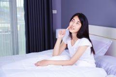 认为在床上的美丽的妇女在卧室 库存图片