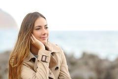 认为在海滩的冬天的美丽的忧郁的妇女 库存图片