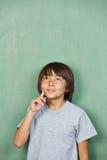 认为在黑板前面的亚裔男孩 库存图片
