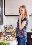 认为如何的妇女烹调鱼 免版税库存照片