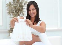 认为孩子的孕妇` s衬衣,坐床 免版税图库摄影