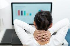 认为年轻的女商人,当研究台式计算机在现代家庭办公室时 免版税库存照片