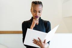 认为拿着一支大白色文件和笔的成功的非洲或黑人美国女商人特写镜头画象在下巴附近 免版税图库摄影