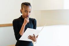 认为拿着一支大白色文件和笔的成功的非洲或黑人美国女商人特写镜头画象在下巴附近 库存照片